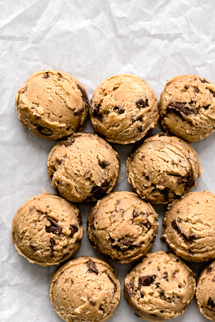 chocolate chip cookie dough balls on parchment lined baking sheet