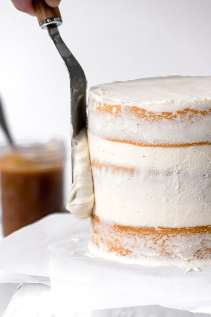 german buttercream being spread on side of caramel layer cake
