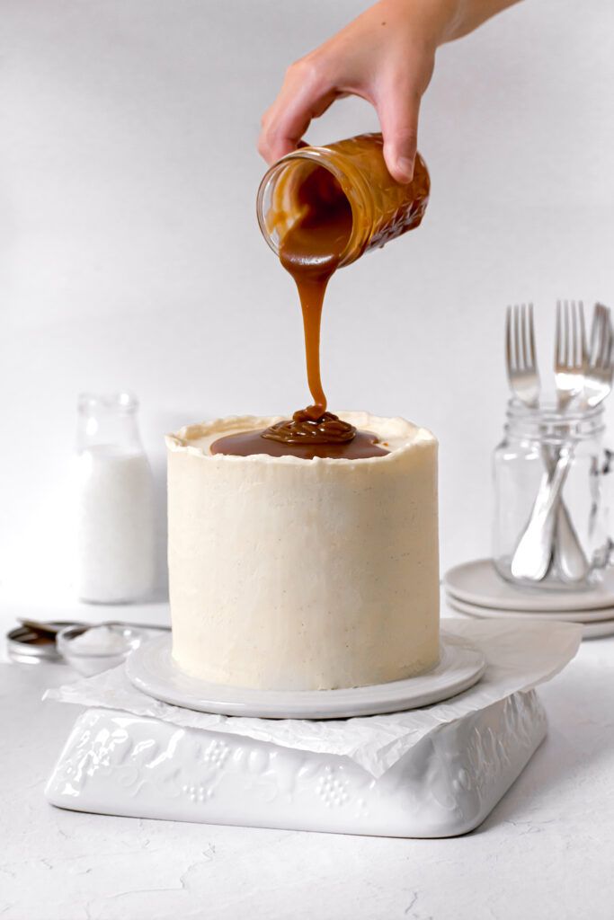 caramel layer cake with caramel sauce being poured on top