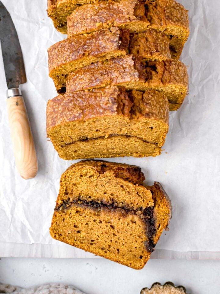 cinnamon swirl pumpkin bread sliced on wood cutting board
