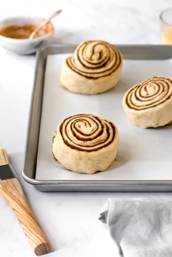 three cinnamon buns on baking sheet