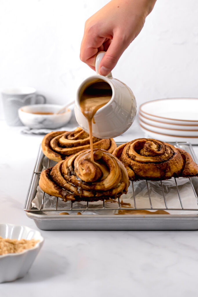 glaze being poured on cinnamon buns
