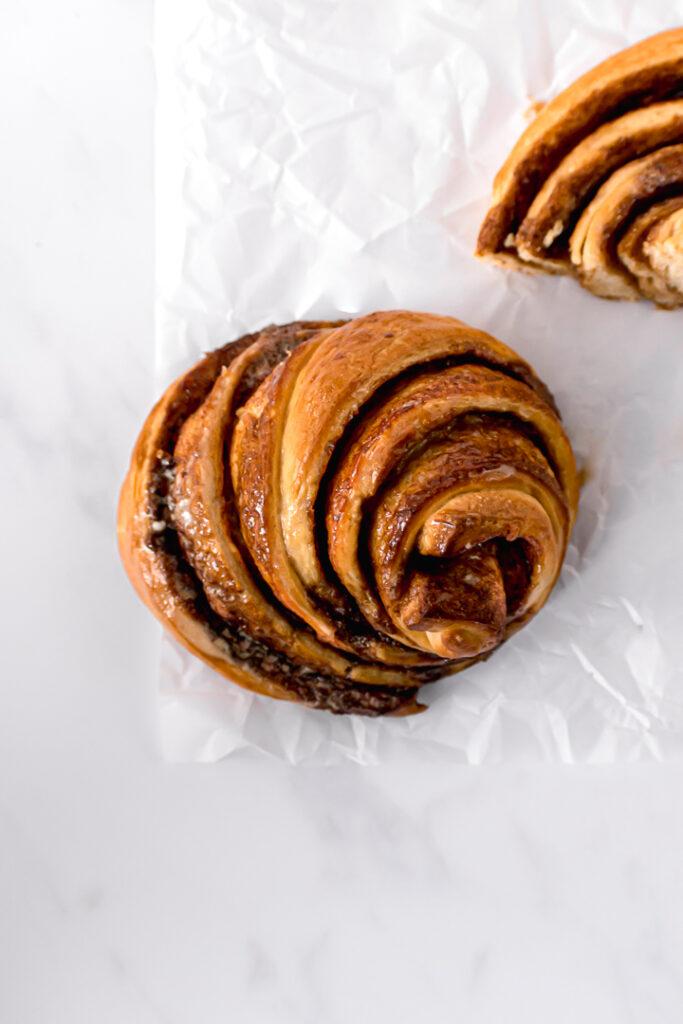 one cinnamon bun on parchment paper