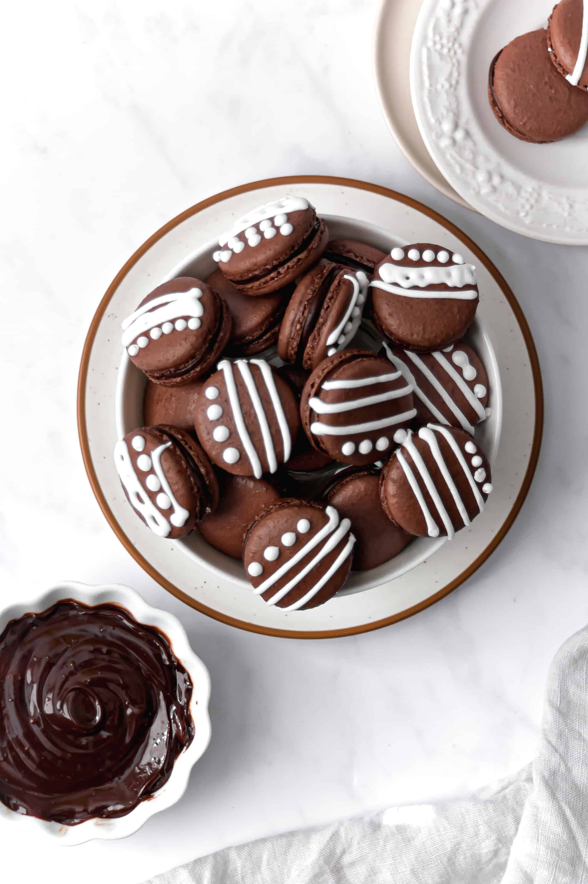 chocolate macarons with white royal icing in a bowl