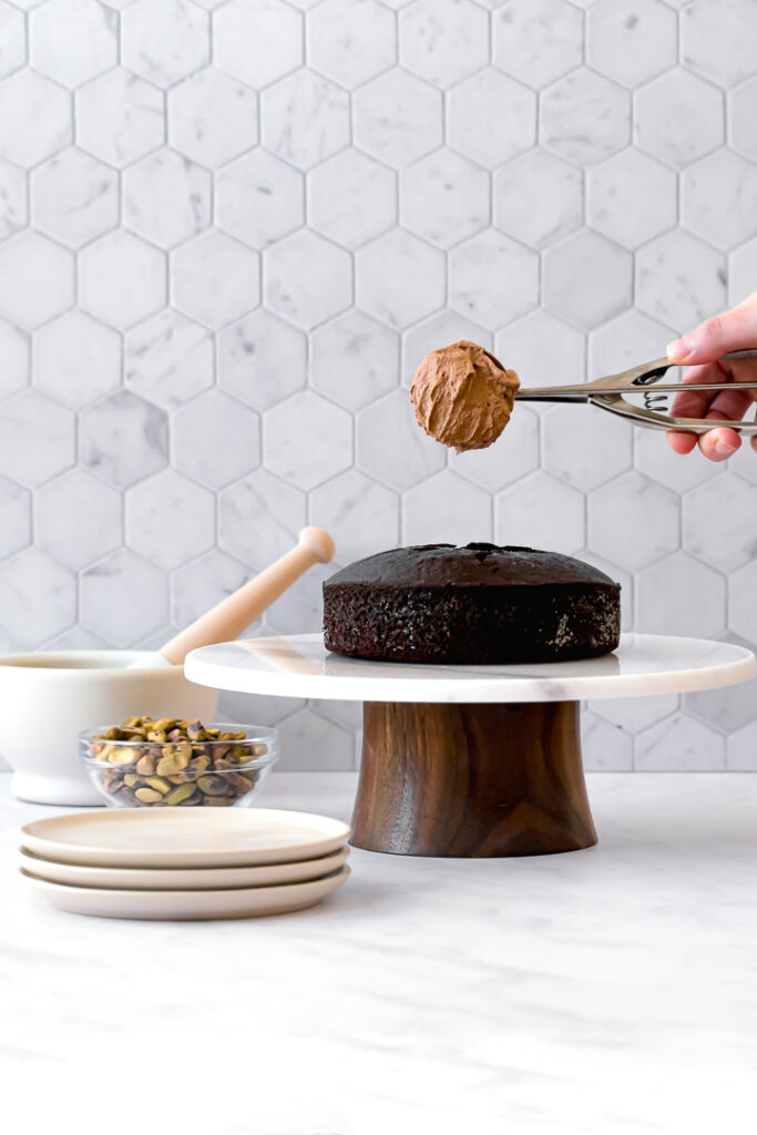 one chocolate olive oil cake layer on cake stand with plates and a bowl of pisatchios