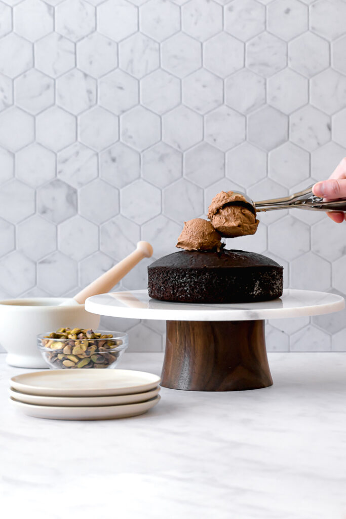 one chocolate olive oil cake layer on cake stand with two scoops of frosting on top