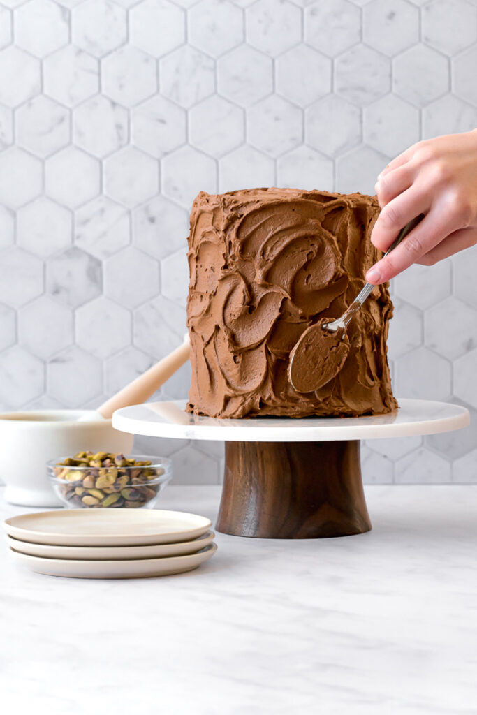 chocolate olive oil cake on cake stand with frosting being spread on the sides