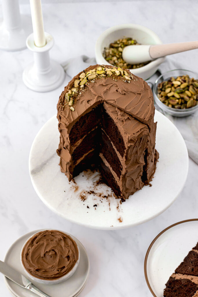 decorated chocolate olive oil cake with pistachios on top and one slice cut