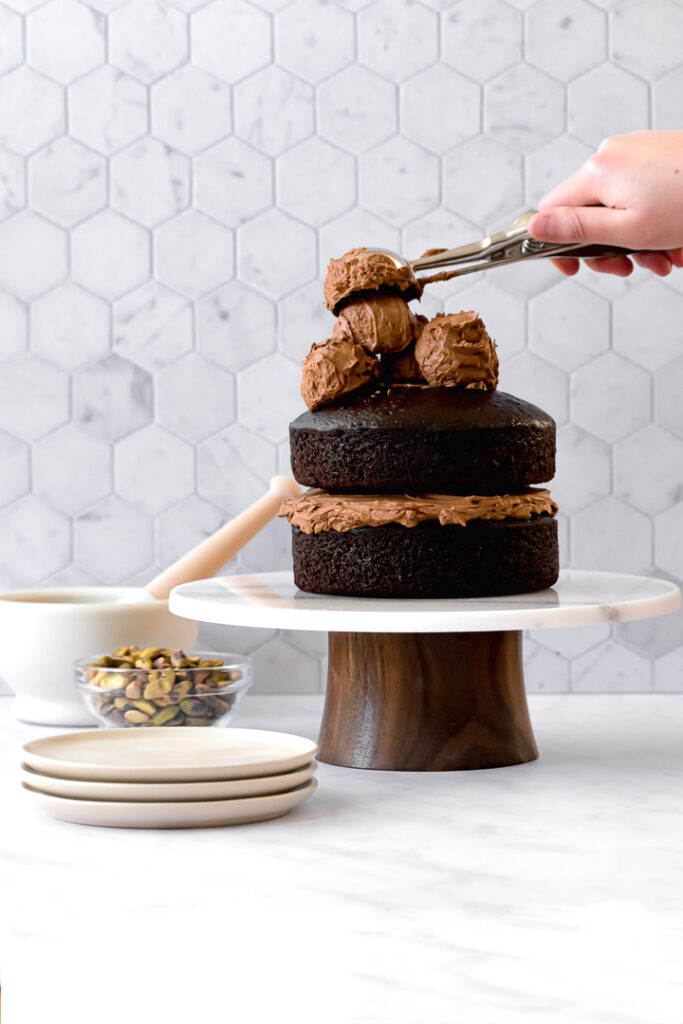 two cake layers on cake stand with four scoops of frosting on top
