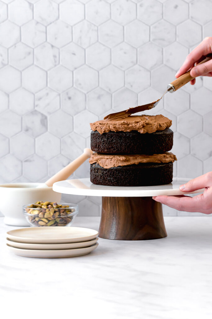 two chocolate olive oil cake layers on cake stand with frosting being spread on top