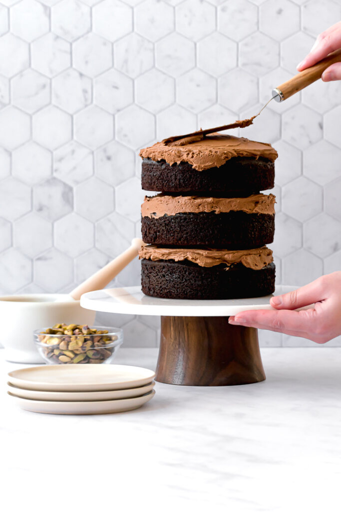 three chocolate olive oil cake layers on cake stand with frosting being spread on top
