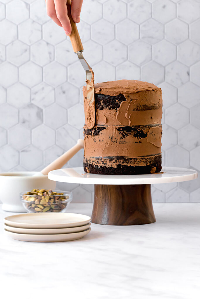 three chocolate olive oil cake layers on cake stand with frosting being spread on the sides