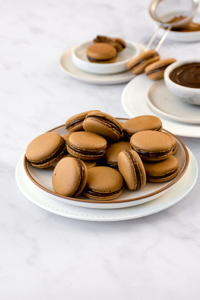 espresso macarons filled with chocolate caramel ganache on two stacked plates