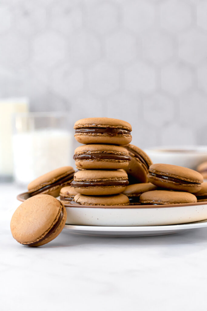 macarons stacked on a plate with a glass of milk in the background