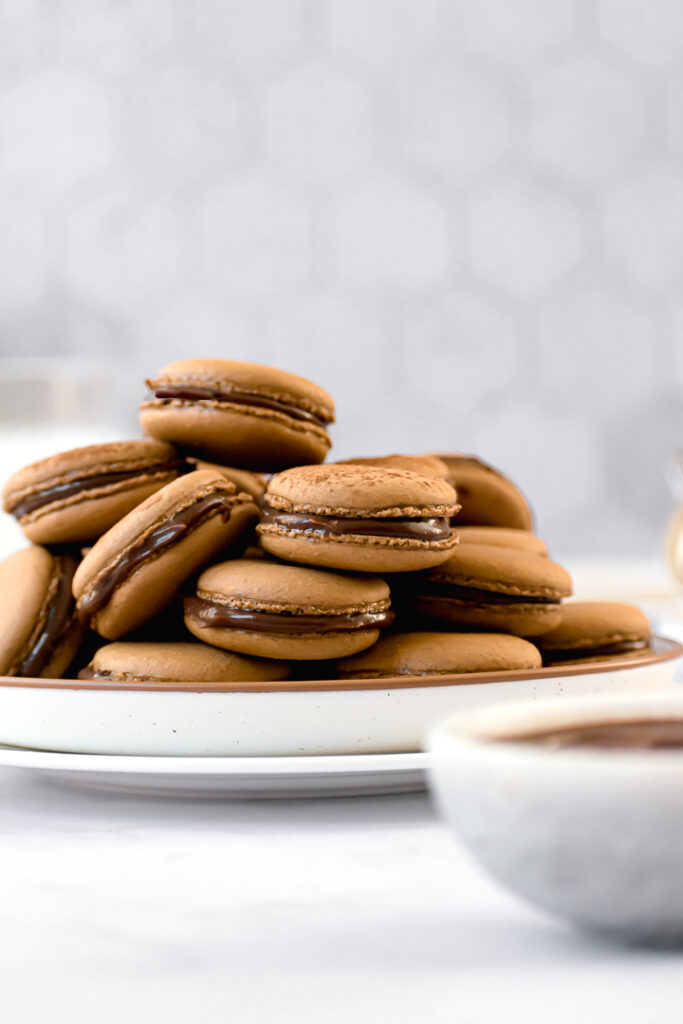 espresso macarons on a plate with a bowl of ganache upfront