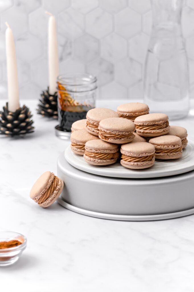 macarons stacked on top of overturned cake pan with candles and a jar of molasses in the background