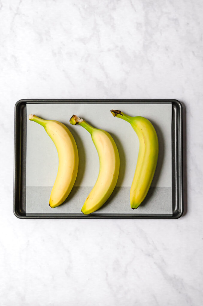 three yellow bananas on parchment lined baking sheet