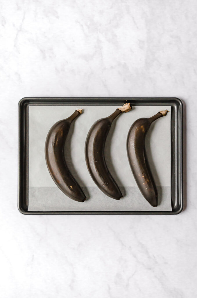 three roasted bananas on parchment lined baking sheet