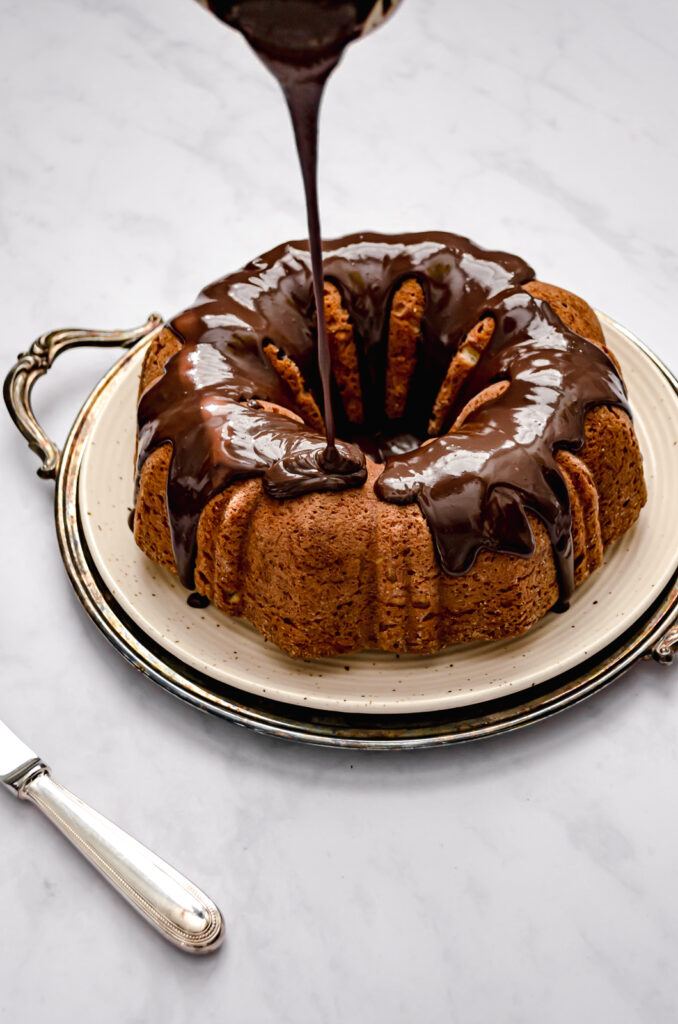 roasted banana bundt cake with chocolate glaze being drizzled on top