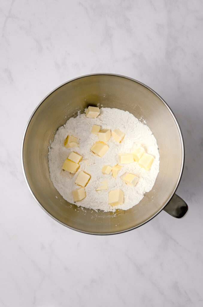dry ingredients with cubes of butter for cake in large bowl