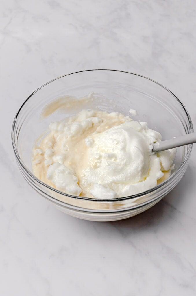 beaten egg whites being folded into cake batter