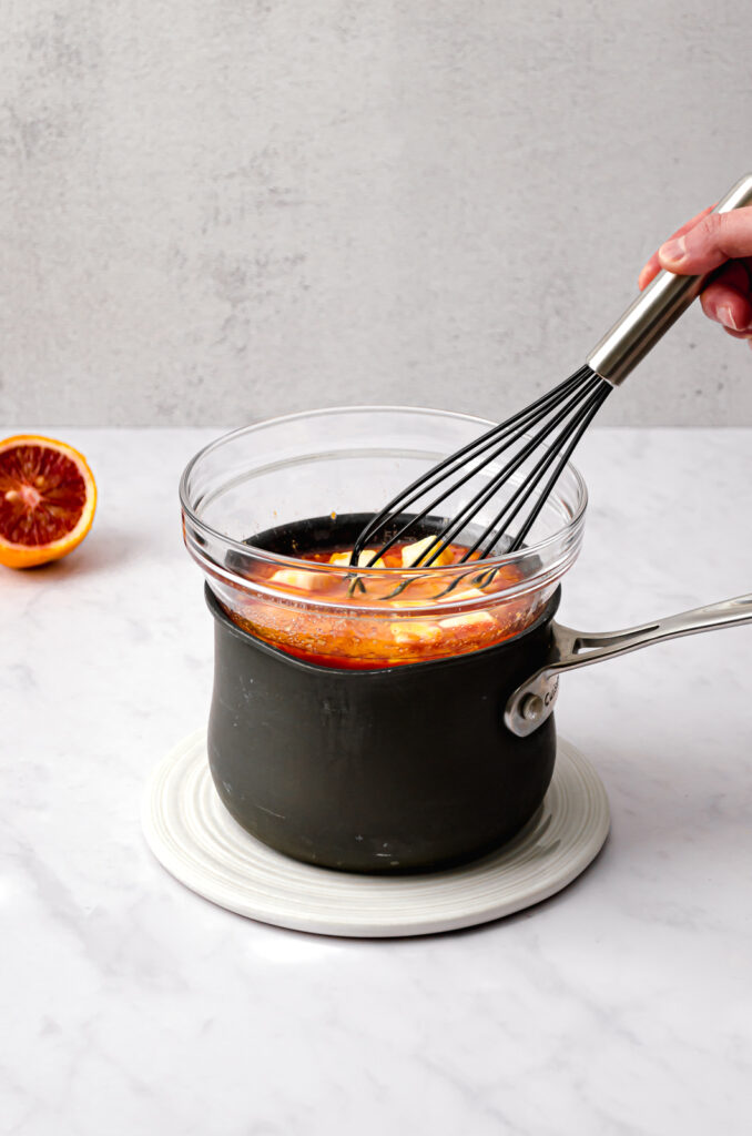 double boiler with blood orange curd ingredients and whisk