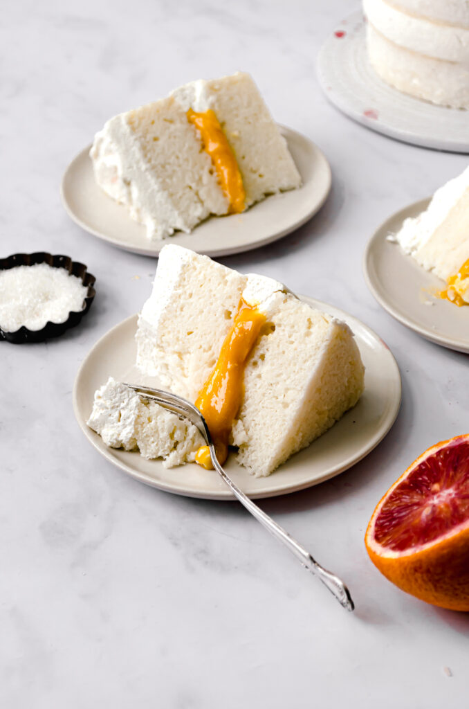 three slices of almond cake and blood orange curd with mascarpone frosting one three small plates