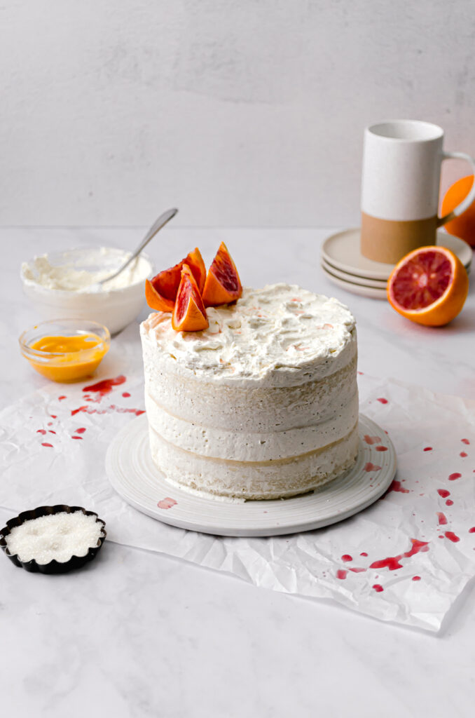 almond cake with blood orange curd and mascarpone frosting with blood orange slices on top