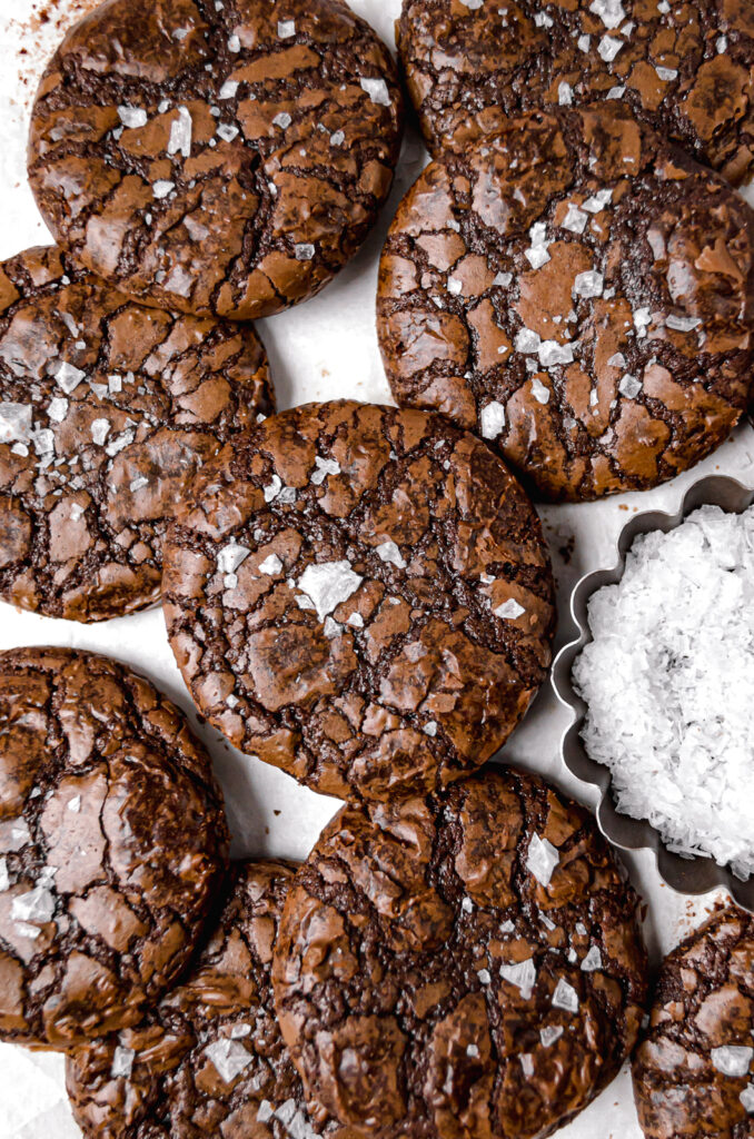 fudgy mocha brownie cookies with flaky sea salt on parchment lined baking sheet