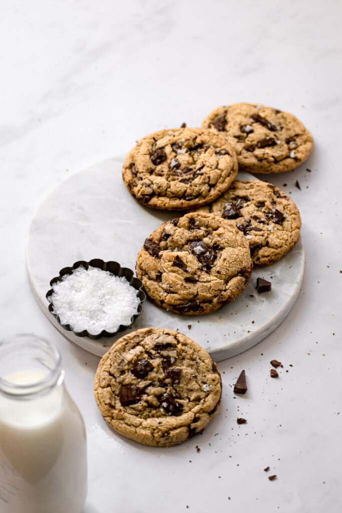 chewy bread flour chocolate chip cookies on marble board with bowl of flaky sea salt