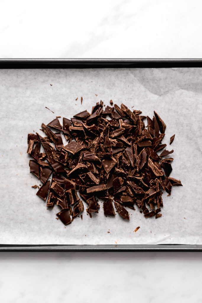 chopped chocolate on parchment lined baking sheet
