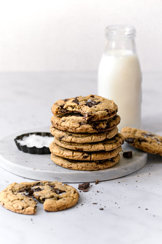 chewy bread flour chocolate chip cookies on marble board with bowl of flaky sea salt and jug of milk