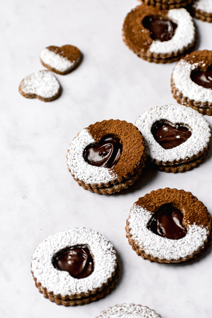 chocolate espresso linzer cookies with powdered sugar and cocoa powder on marble background