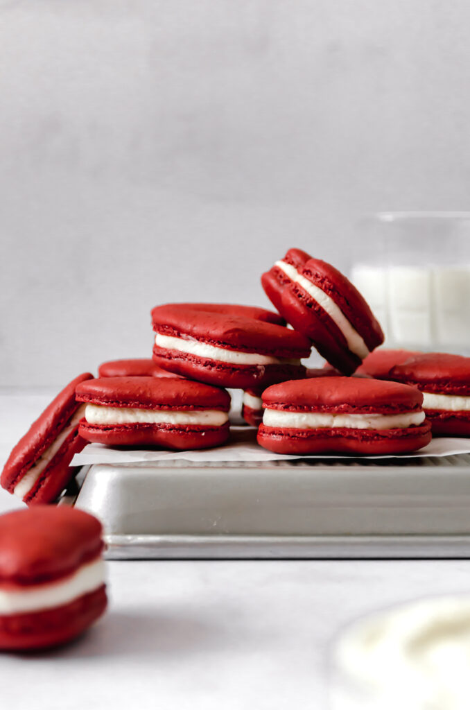 red velvet heart macarons with mascarpone frosting on parchment lined baking sheet