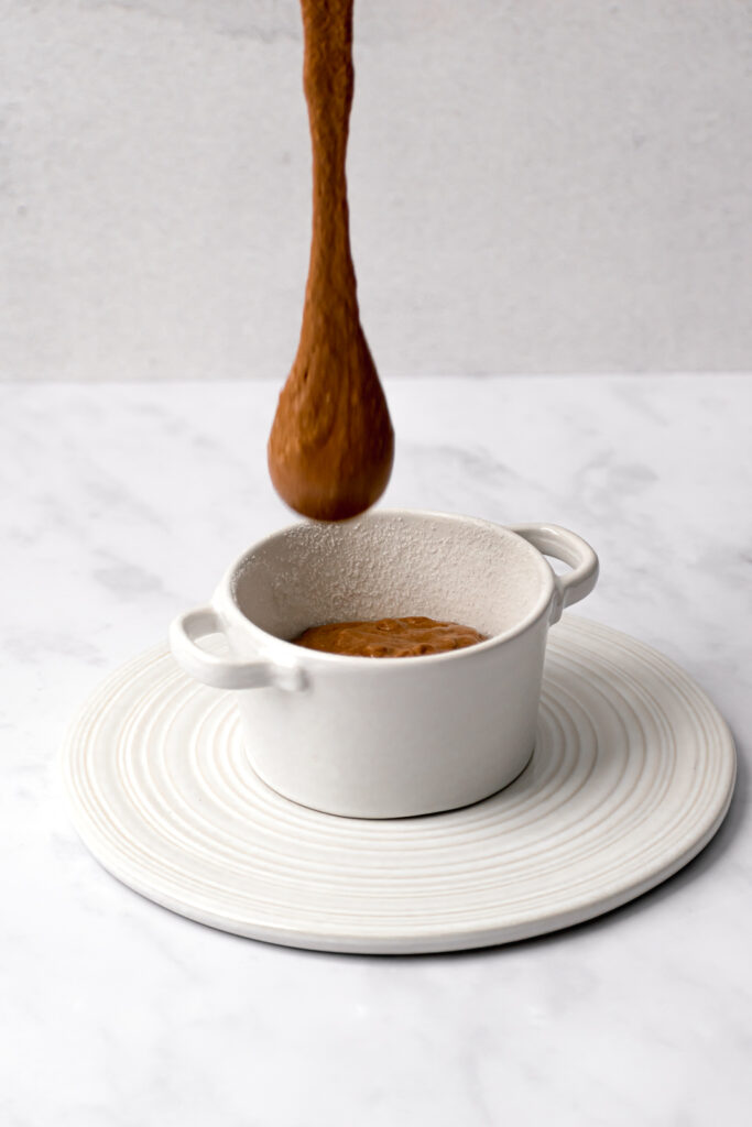 soufflé batter being poured into a white ramekin on top of a white trivet