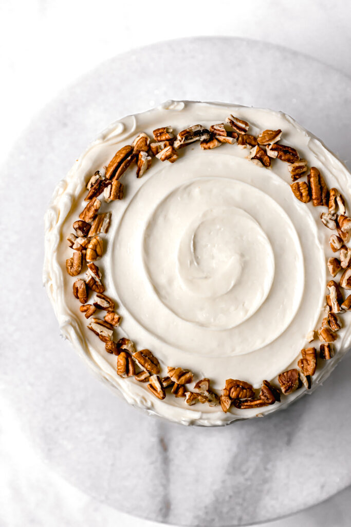 ginger sauerkraut carrot cake decorated with cream cheese frosting and pecans