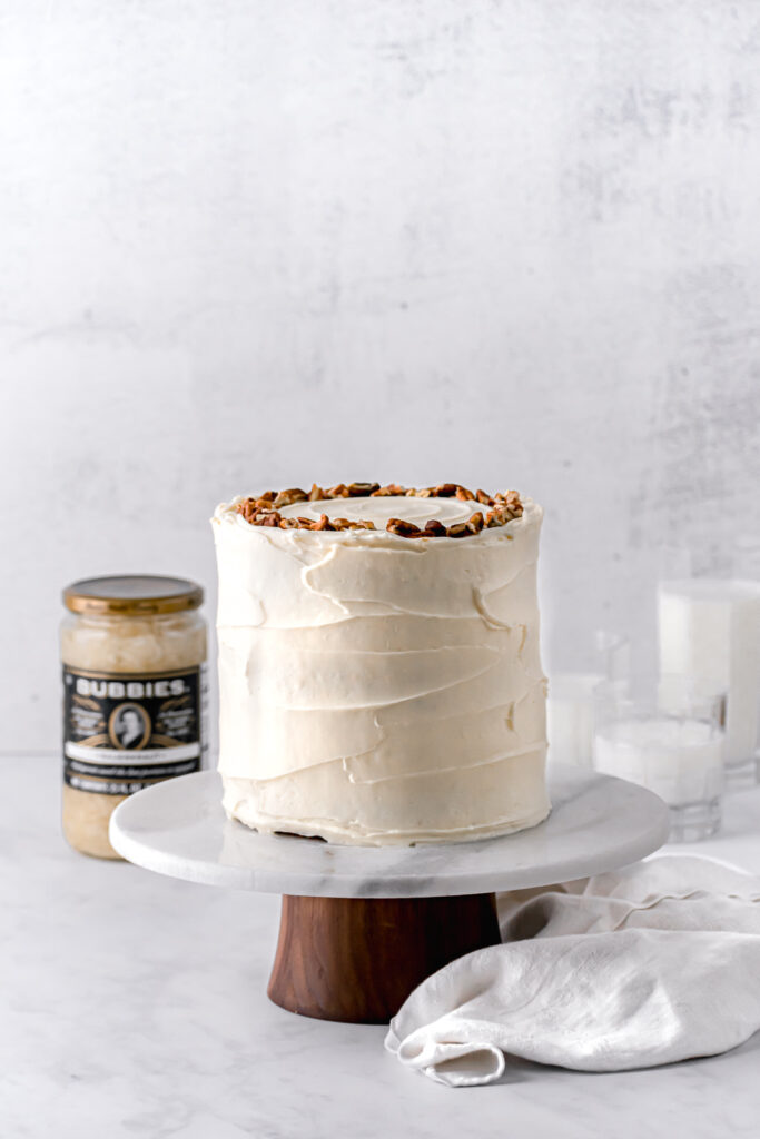 ginger sauerkraut carrot cake with cream cheese frosting on marble & wood cake stand