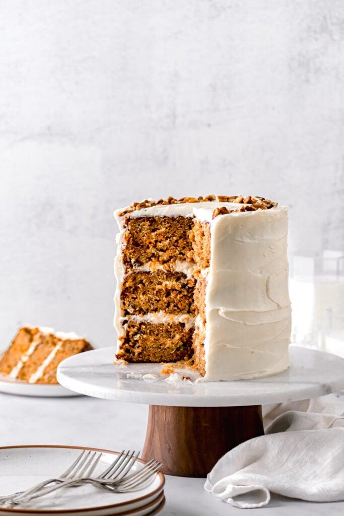 cut ginger sauerkraut carrot cake on marble & wood cake stand