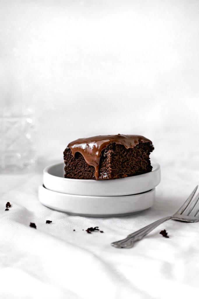 piece of dark chocolate malt snack cake on stacked white plates