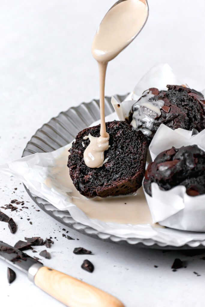 one double chocolate tahini muffin cut open on a plate with tahini being drizzled on top