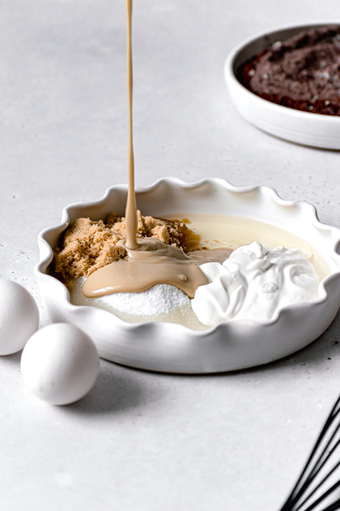 tahini being poured onto sugars and wet ingredients in white ruffled dish