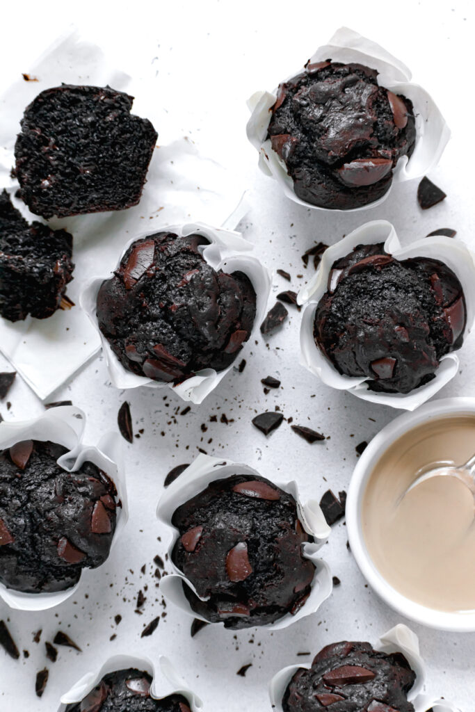 double chocolate tahini muffins with chopped chocolate everywhere and a bowl of tahini