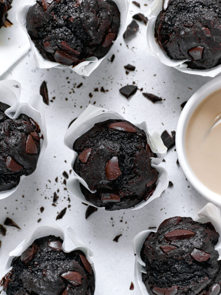 double chocolate tahini muffins with chocolate sprinkled everywhere and a bowl of tahini
