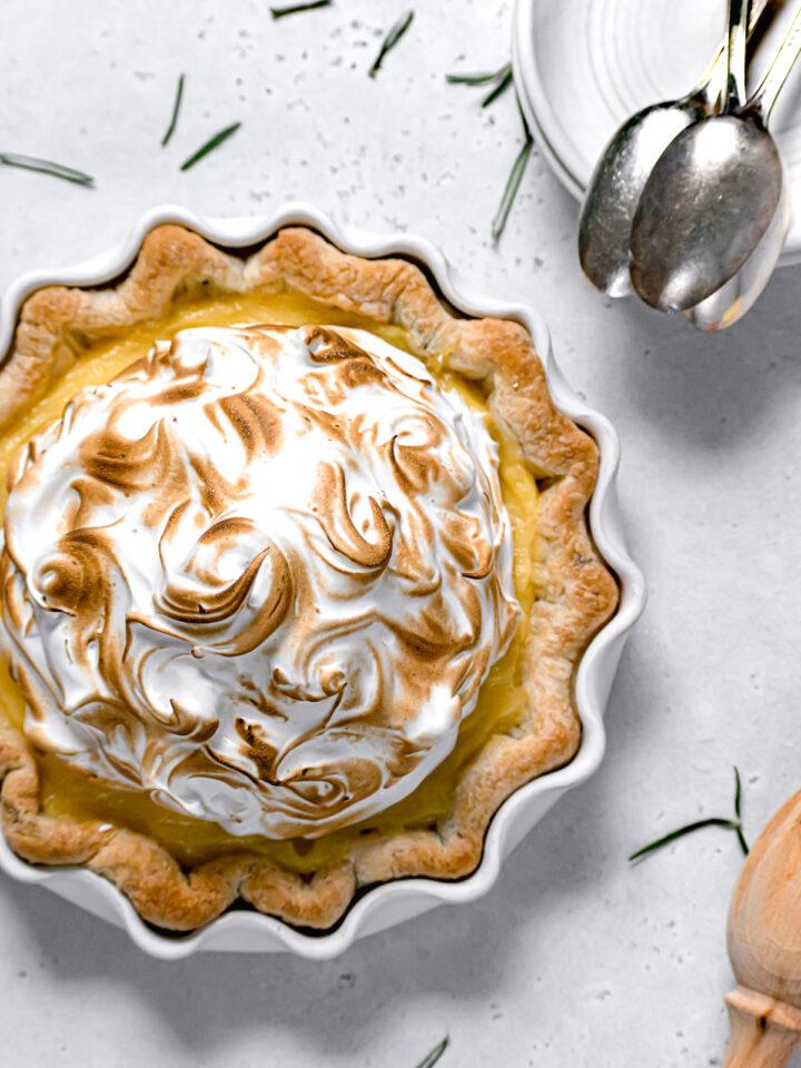 lemon meringue pie with fresh rosemary crust in white pie dish