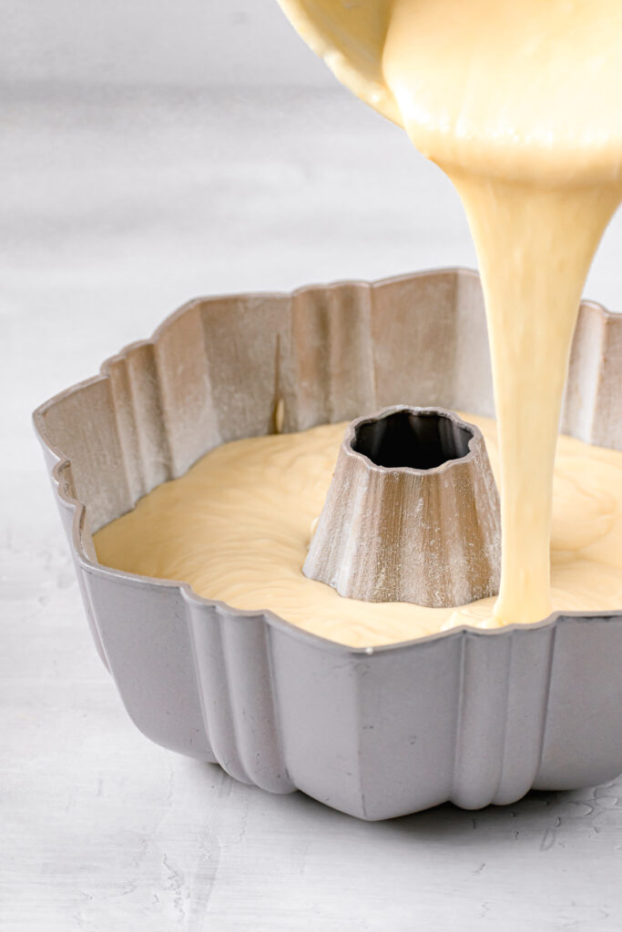 rum cake batter being poured into bundt pan