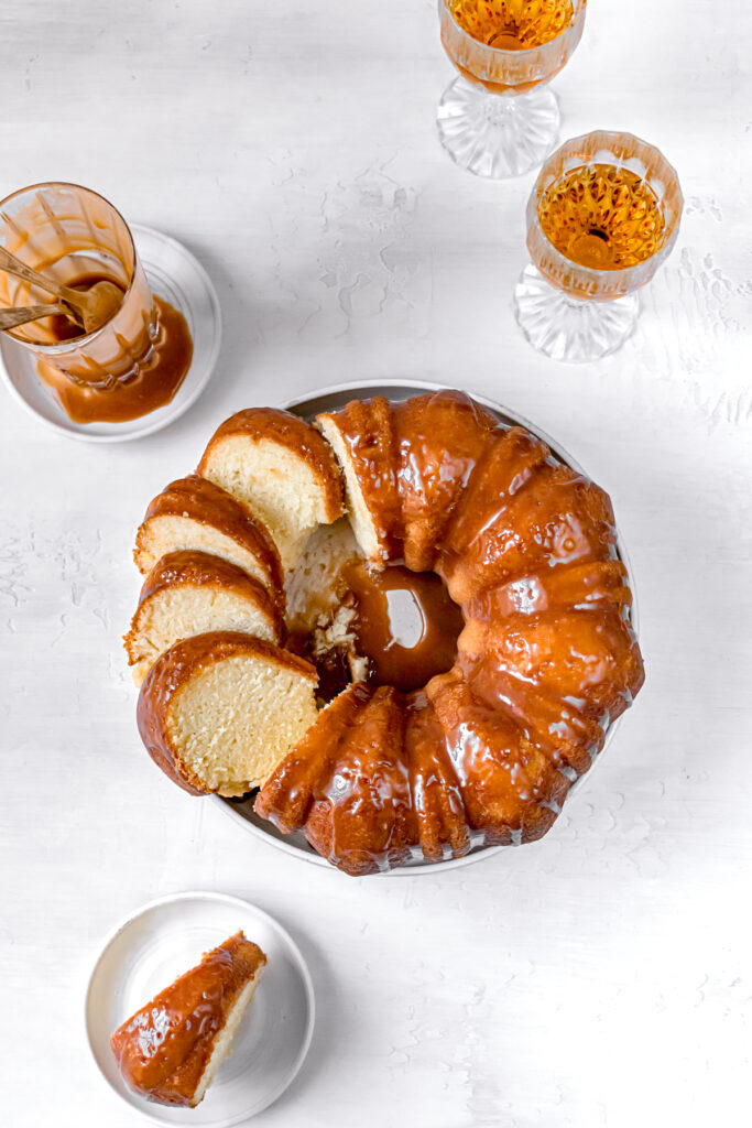 sliced bundt cake with glasses of rum and cup of caramel sauce