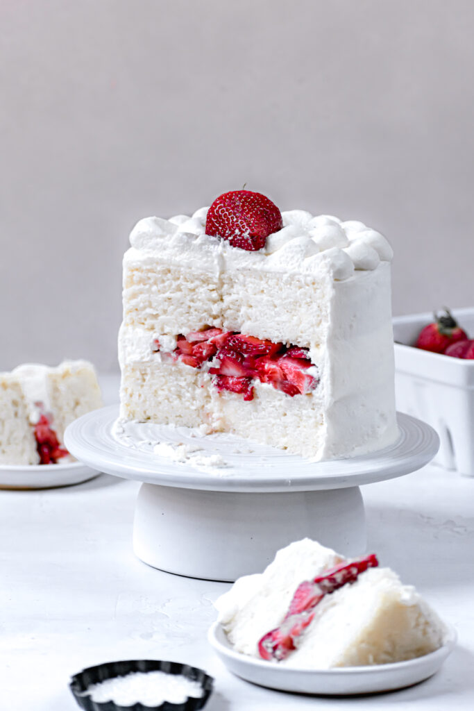 sliced cake on white cake stand to reveal texture of cake and fresh strawberry filling