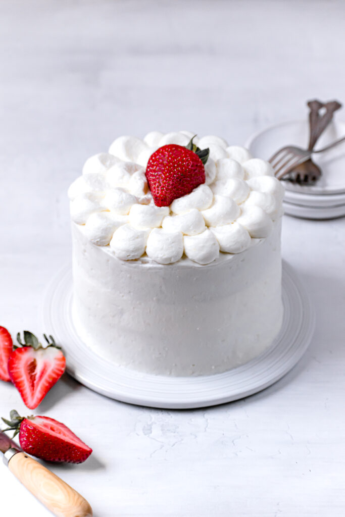 white cake with strawberries on white plate