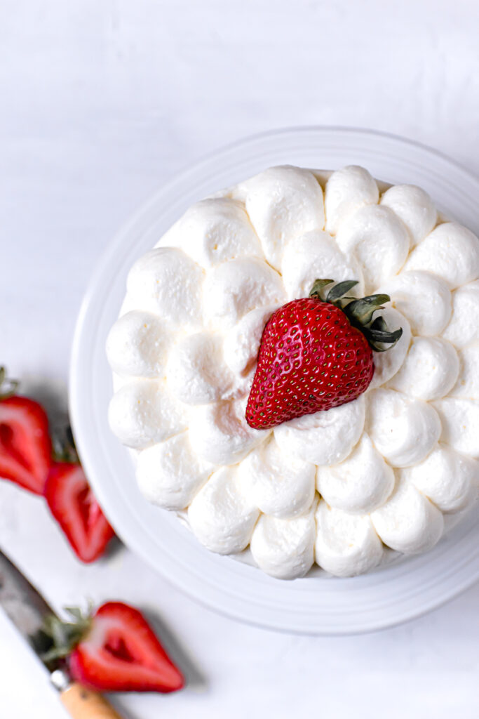 close up of the top of the decorated cake with a strawberry in the center