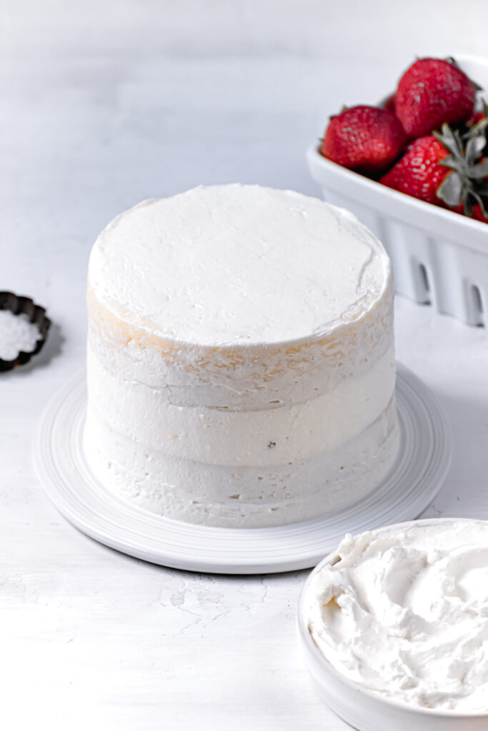 crumb coat of frosting spread all over cake